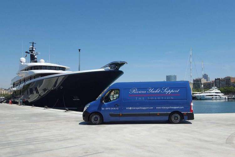 Blue Riviera Yacht Support van parked in a port next to a superyacht