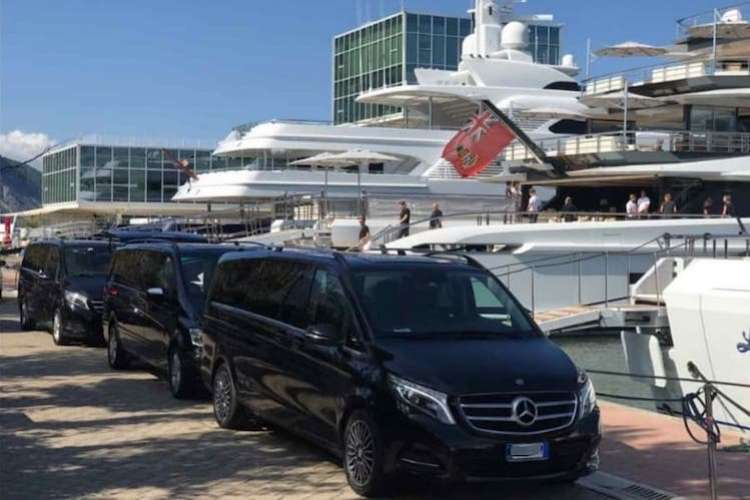 Three nlack mercedes vans parked in front of a superyacht port