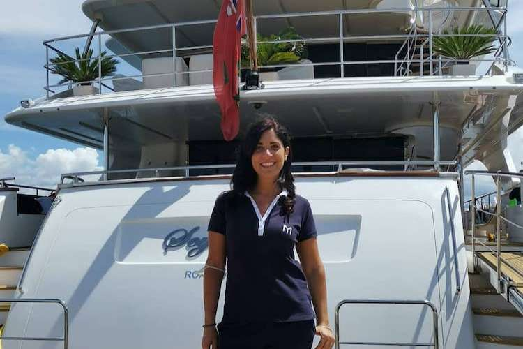 Dark haired woman standing in front of a superyacht
