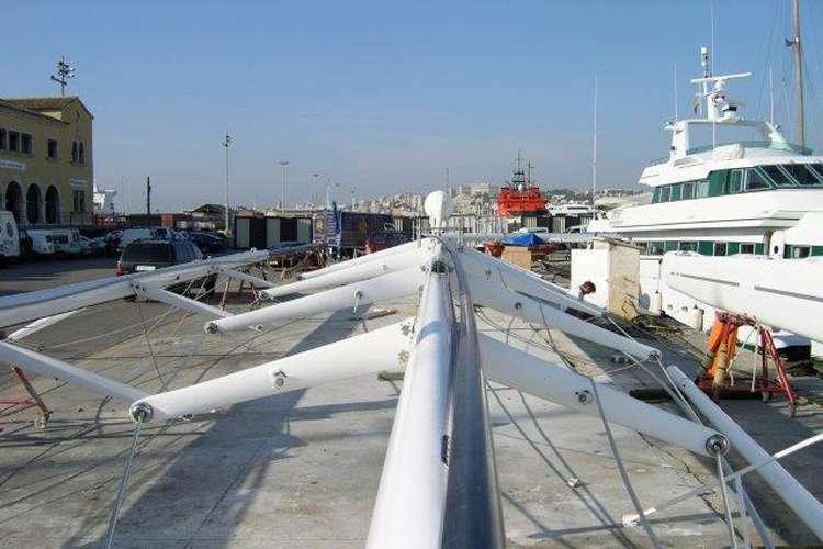 Sailing mast laid on a shipyard platform.