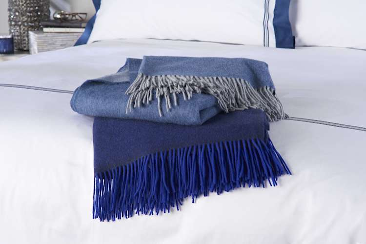 Blue wool blanked laid on a white blue bed linen