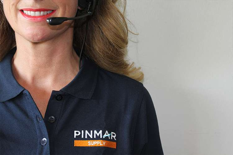 Woman wearing a dark blue Pinmar Supply shirt and a head set smiling