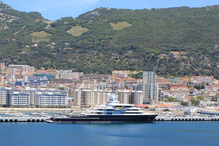 Mega yacht anchored close to a shore with a city in the background