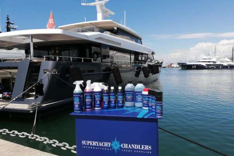 Superyacht chandlers biodegradable cleaning products on a stand with a superyacht in the background