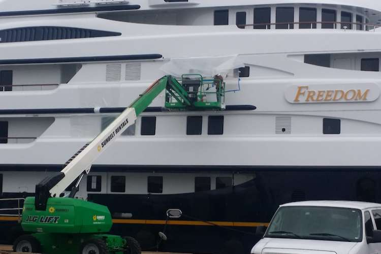 Men lifted up with a small green crane and working on the side of a mega yacht