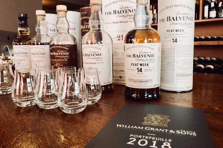 A range of hand-crafted the Balvenie single malt Scotch whiskies on a table with glasses
