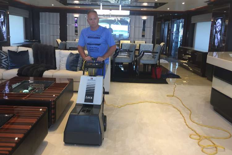 JC's Carpet Cleaning expert cleaning a carpet in a superyacht.