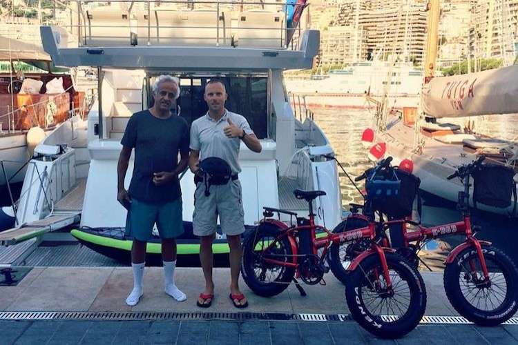 Two men standing if front of a yacht with MonecoBike rental e-bikes next to them