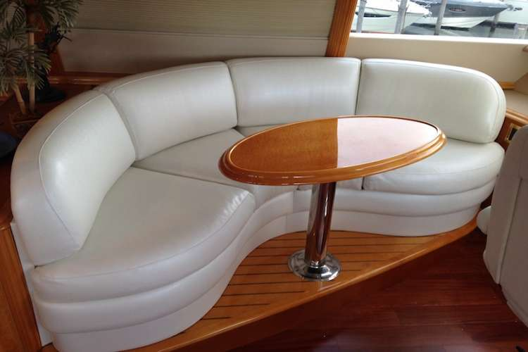 White leather sofa and cherry table in a yacht living room