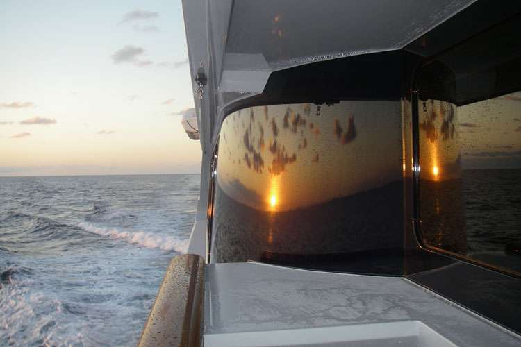 Sunset mirroring from a superyacht window.