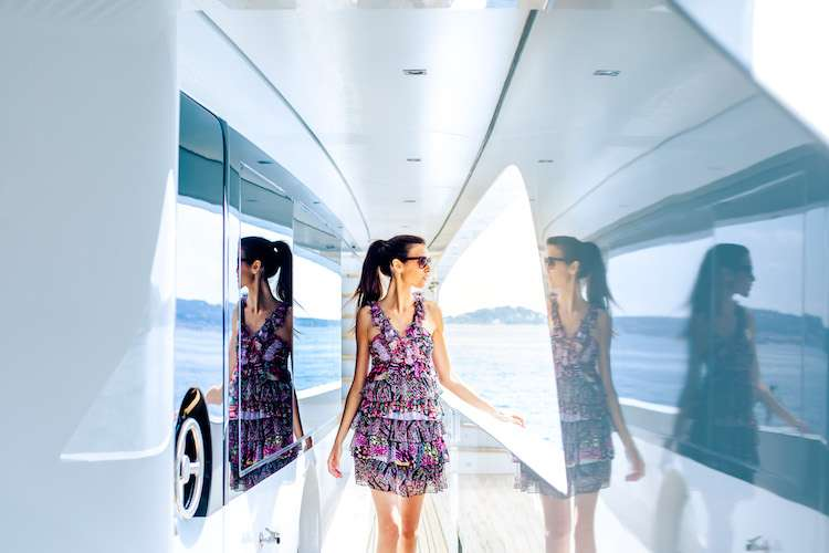 Dark haired woman walking on a yacht deck looking to the sea