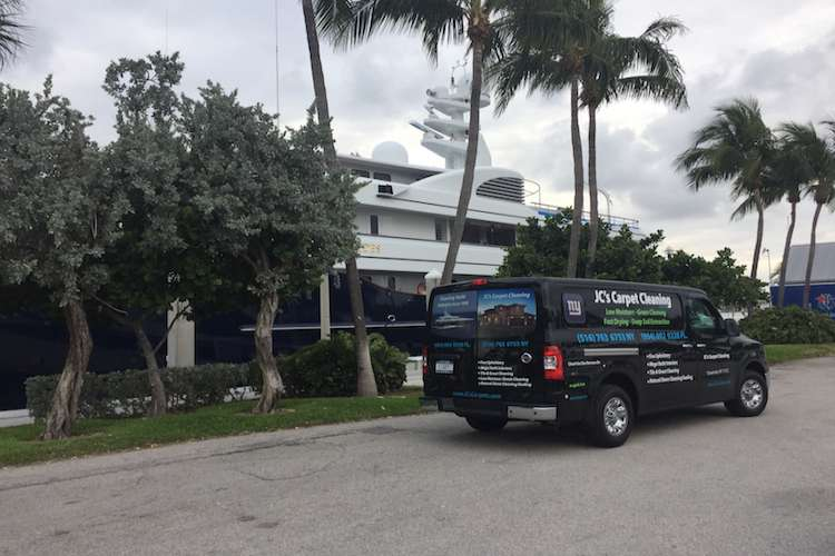 JC's Carpet Cleaning van parked next to a berthing superyacht.