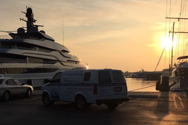 JC's Carpet Cleaning van parked next to a superyacht in a port in a sunset.