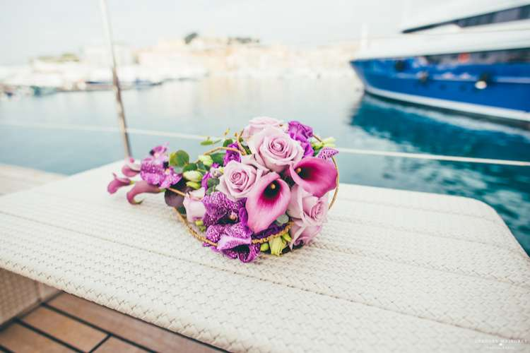 Flower arrangement with mix of pink flowers on a superyacht deck table
