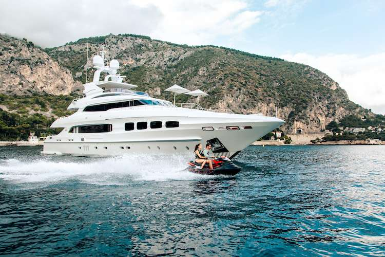 Water jet cruising in front of a superyacht