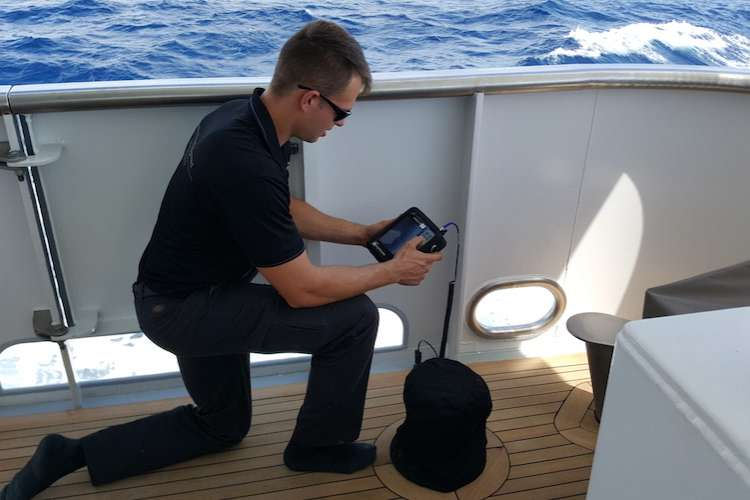 An AME specialist on a superyacht deck doing analysis on a tablet size monitor