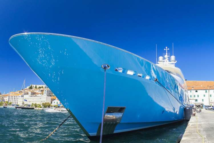 Image of a mega yacht's blue bow and hull with a port on the background.