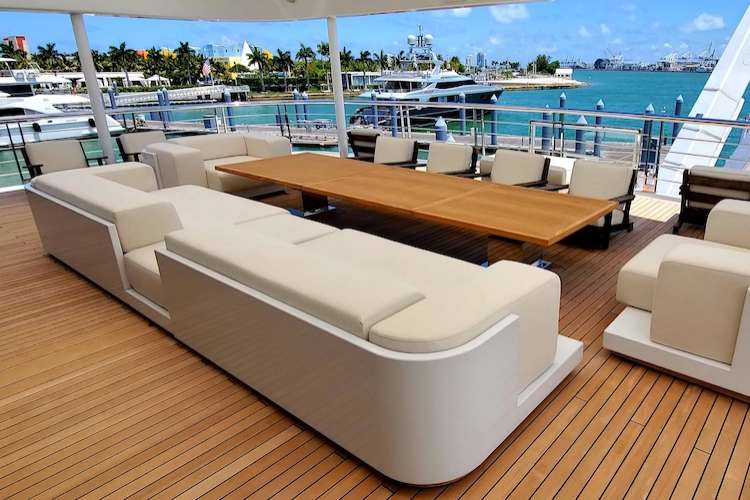 Superyacht deck with long teak coloured table and beige couch and armchairs from Eclipse