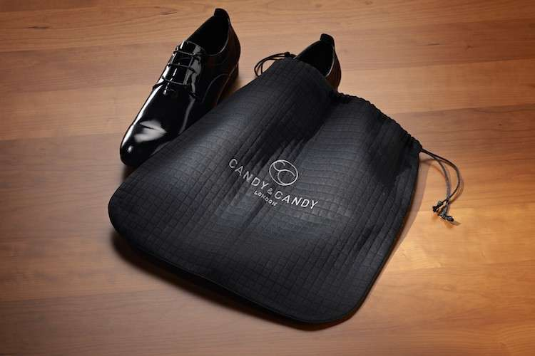 Black shoe bag and a black patent leather shoes on a floor.