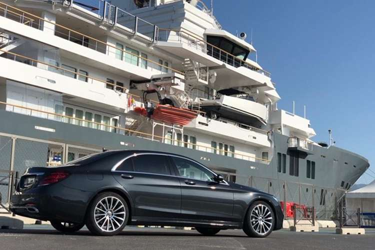 side view of a luxury mercedes outside a superyacht
