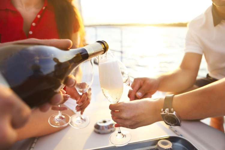 Women sitting around a table on superyacht deck champagne being poured into their glasses.