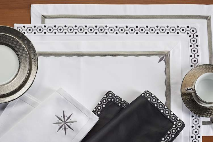 Table linen with embroidery laid on table with fine coffee china.