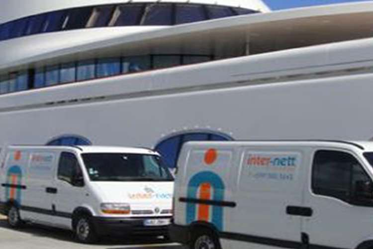 Two white Inter-nett vans parked in a port next to a mega yacht