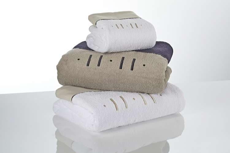 Three fluffy towels with embroiling from Heirlooms in a pile.