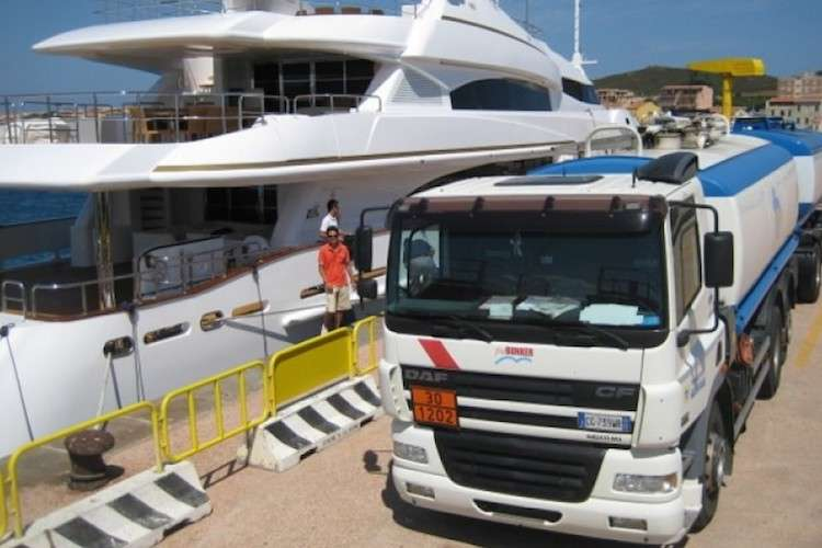 Fuel truck fuelling a superyacht in a dock