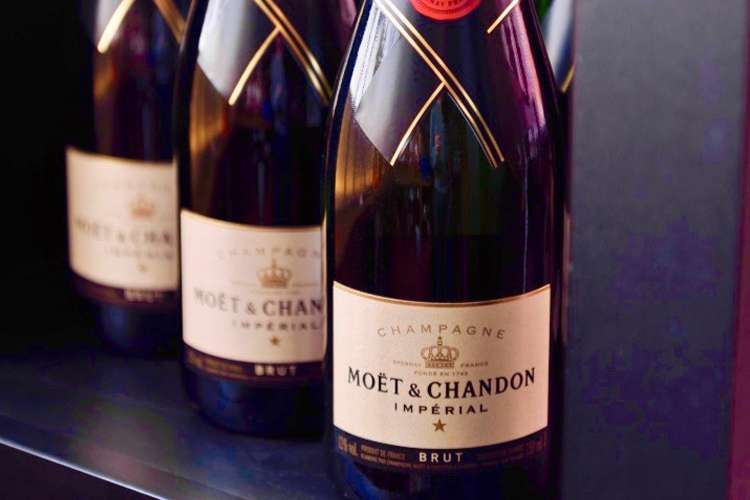Three Moet & Chandon Imperial Champagne bottles in a row on a table