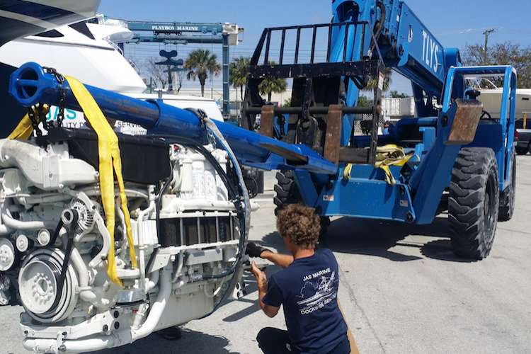 Man attaching an engine to a small crane for lifting it
