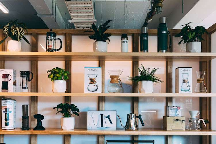 Image of a shelf with books and green flowers in a trendy Good Karma coffee shop space.