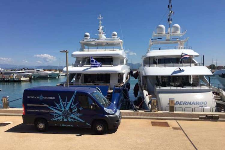 Blue superyacht provisions van parked in a dock in front of two superyachts