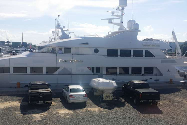 Superyacht docking in a shipyard with cars parked in front of it