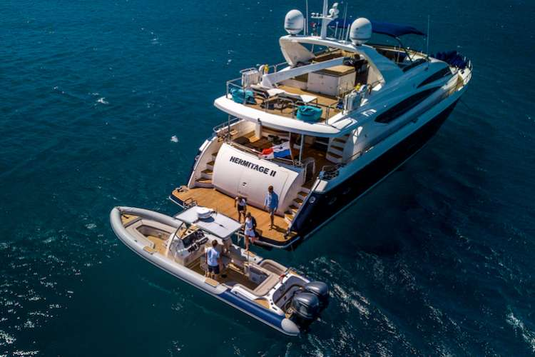 People stepping on a Aerial image of a ribeye tender parked next to a superyacht stern