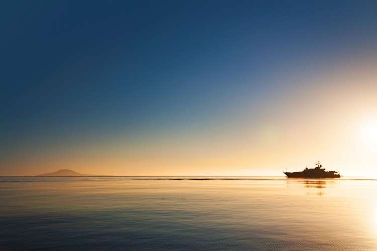 Image of a distant superyacht cruising in a sunset.