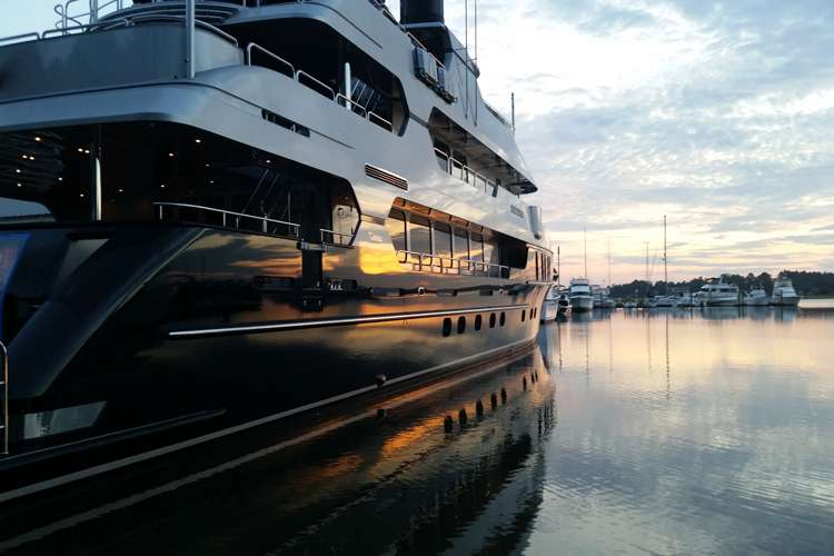 Image of a superyacht berthing in port during sunset