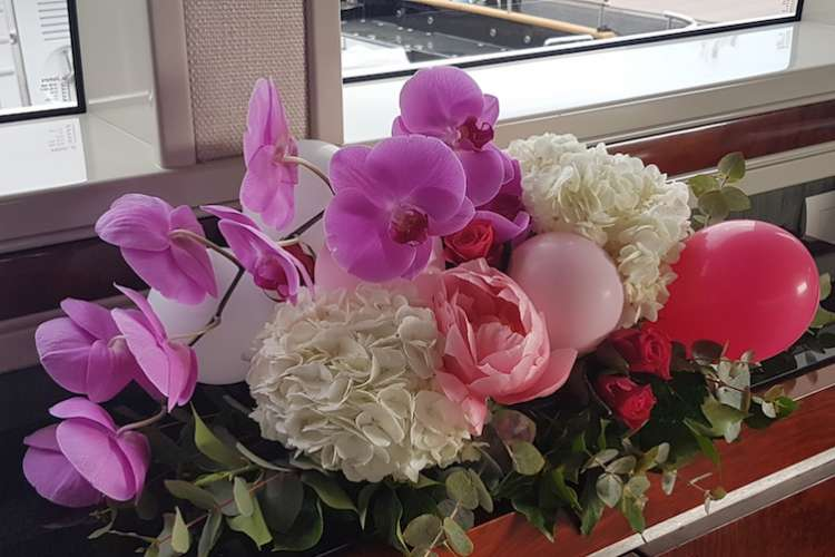 Flower arrangement of purple orchid and white hortensia with pink balloons
