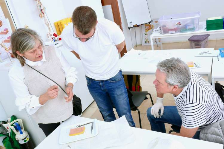 Dr. Johanna Clark discussing with two men in a training classroom.
