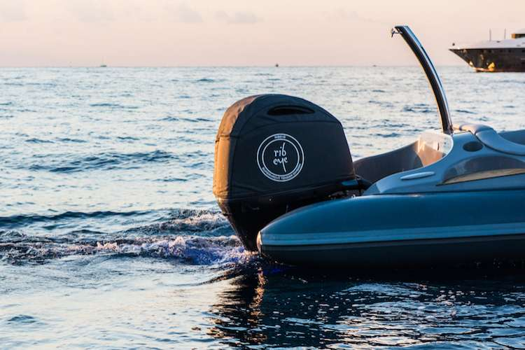 Stern of a Ribeye boat in an orange sunset light with the Ribeye logo in the black motor