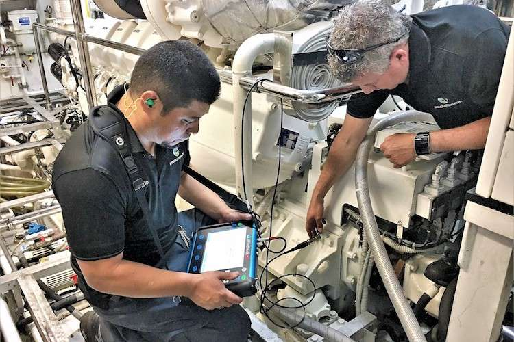 Two engineers working on in machine room and looking at the tablet size monitoring screen