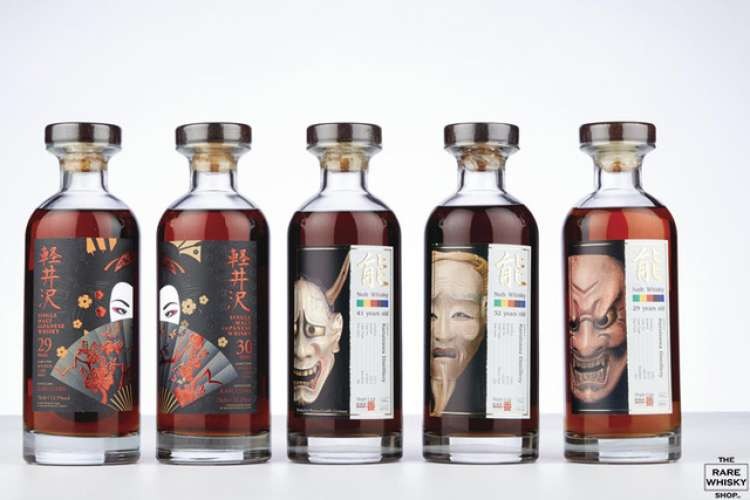 Macallan whisky bottles with an image of men and women drinking Macallan whisky on yacht deck