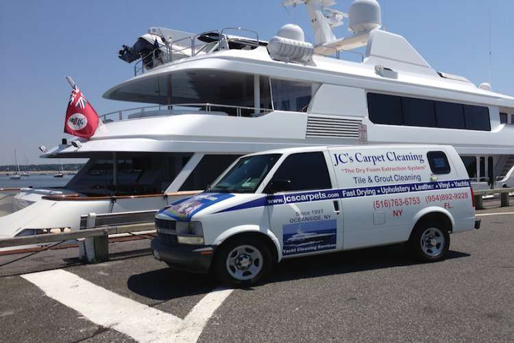 JC's Carpet Cleaning van parked next to a superyacht in a port.