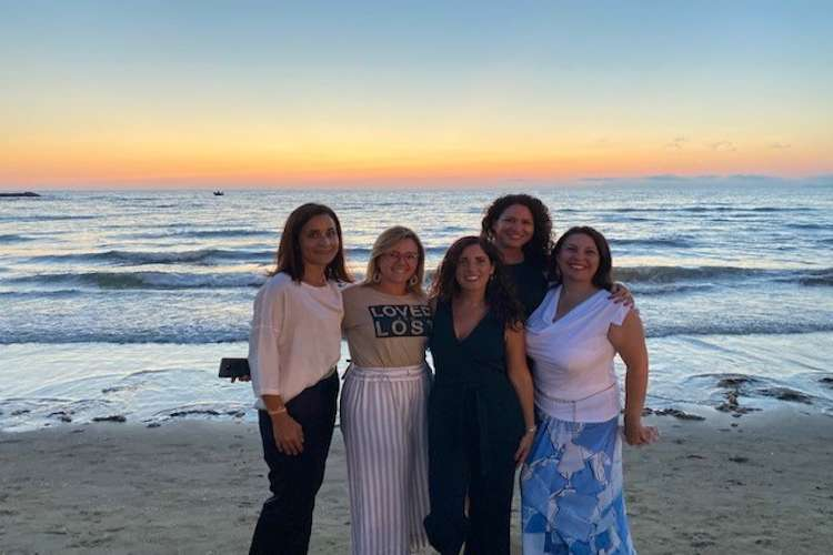 5 women standing on the beach at sunset