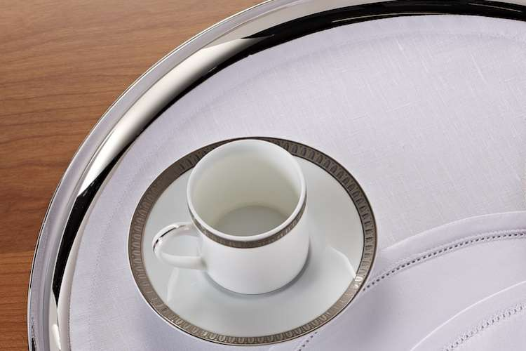 Tray liner and coffee cup on a silver tray.