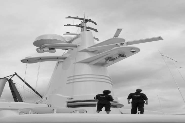Two engineers on standing below a superyacht radar and communication tower looking up.