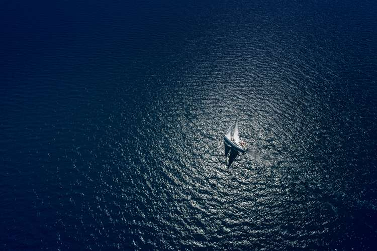Image of a sailing yacht in the sea during the night illuminated by the moon.