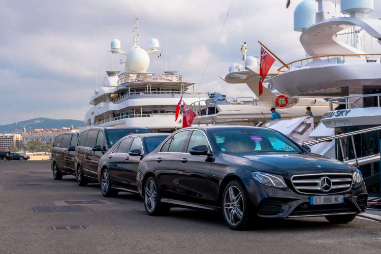 Luxury cars lined up at the back of superyachts