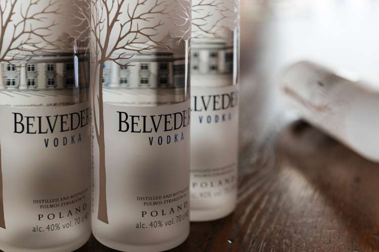 Three Belvedere Vodka bottles in a row on a table