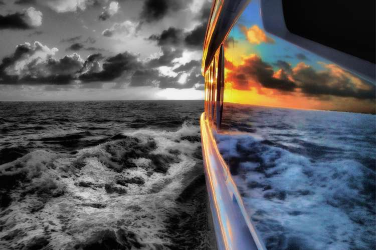 Black and white sea and sky mirroring from a yacht hull in colours.
